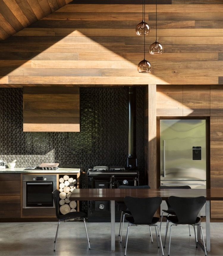 River-rimu kitchen cabinets pair well with a stone benchtop, stainless steel appliances, and an eye-catching splash glass.