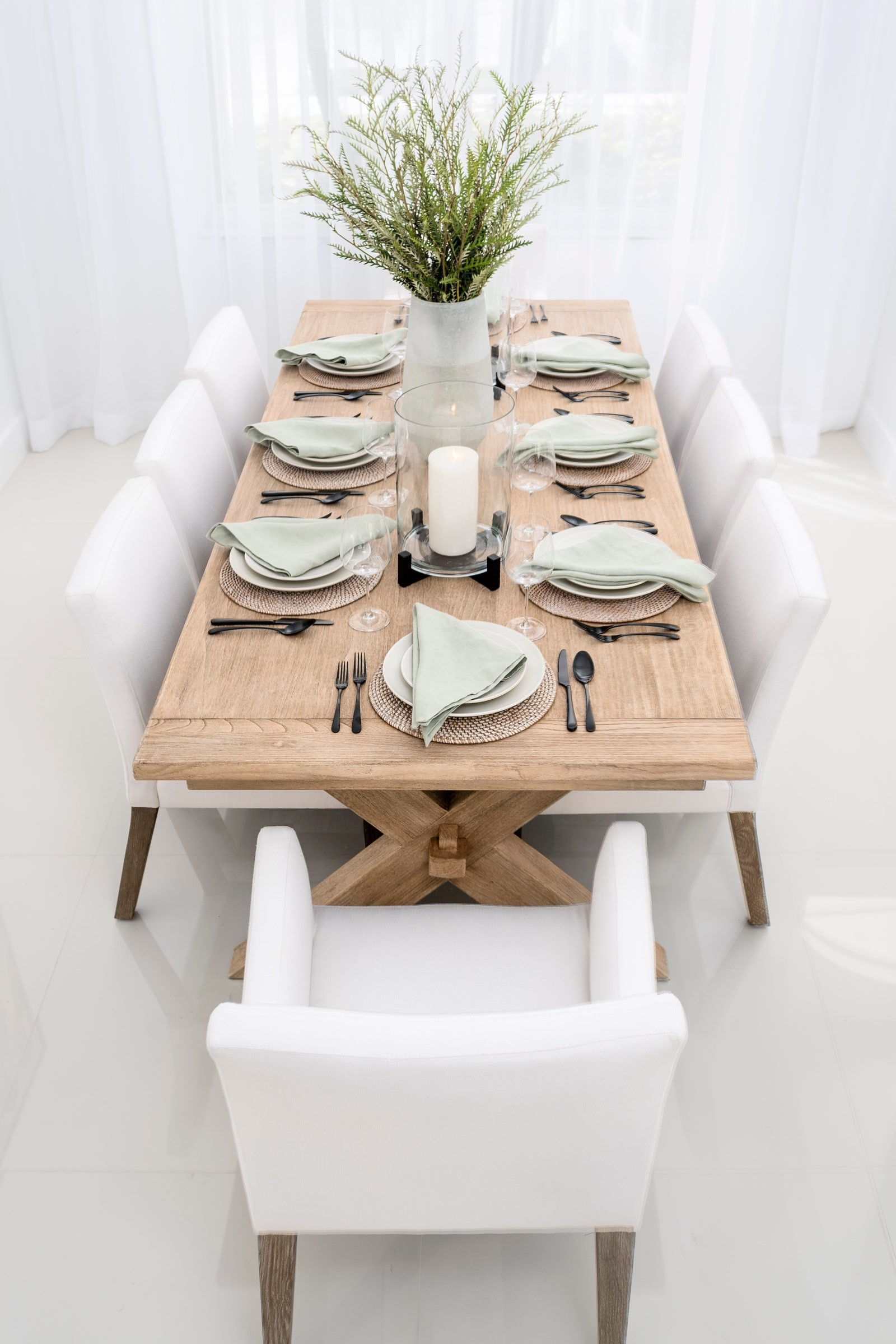 All white dining area with armchaired dining charis and wooden decorated table