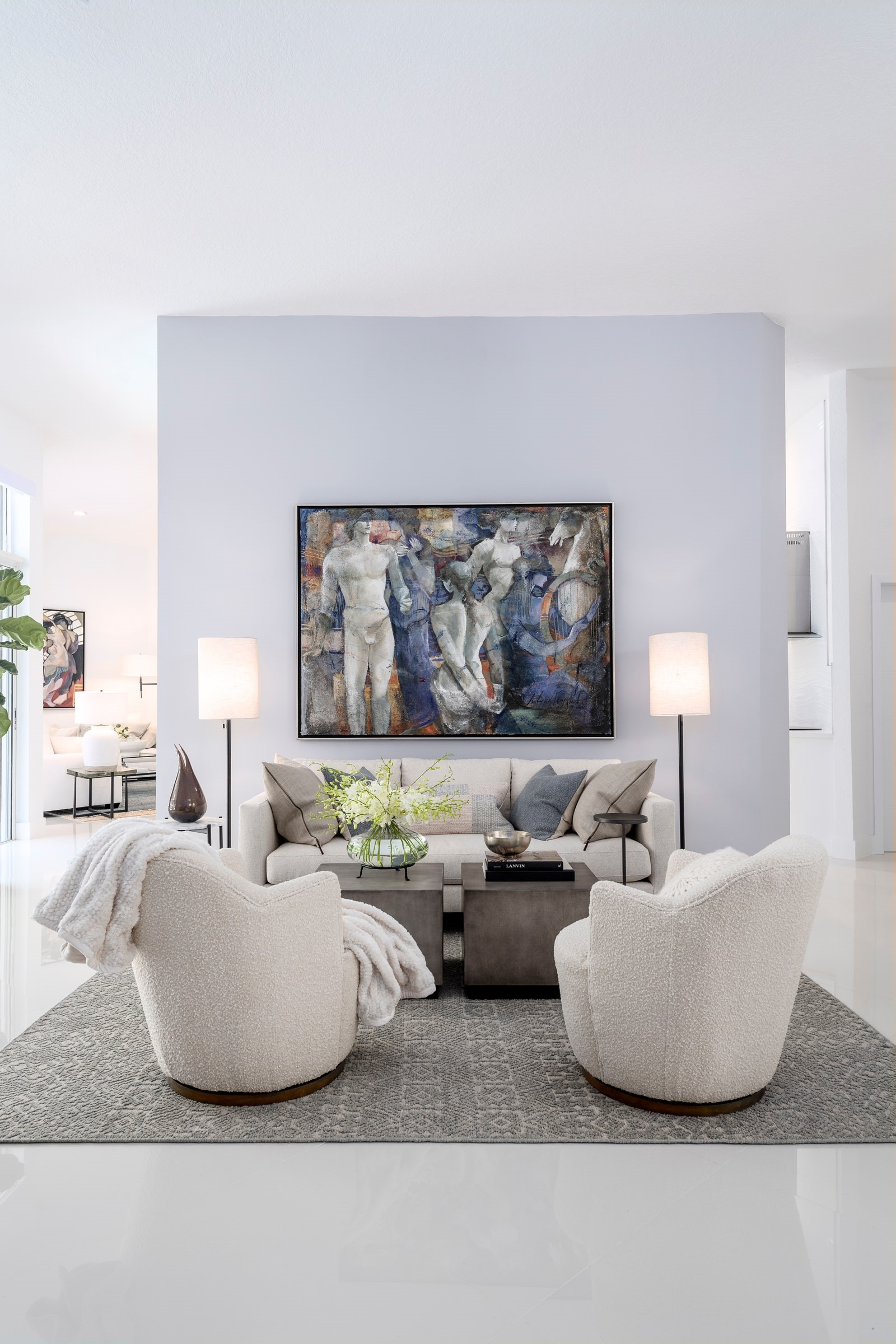 The living room lives up to its traditional Miami vibes with cool white walls and polished white marble floors. On the feature wall, a painting of Giselle transforms the room from cool elegance to WOW