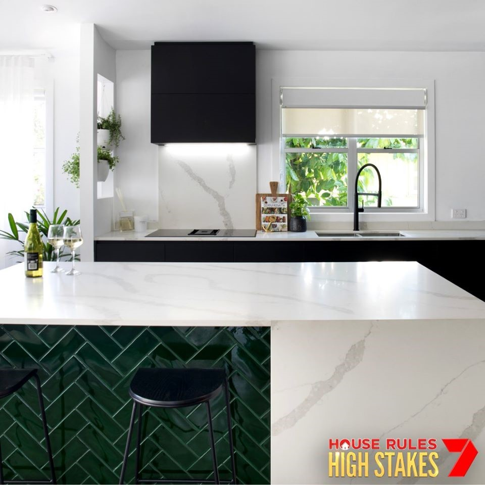 Sleek integration of white, black, and jade green create a polished kitchen that is light and airy
