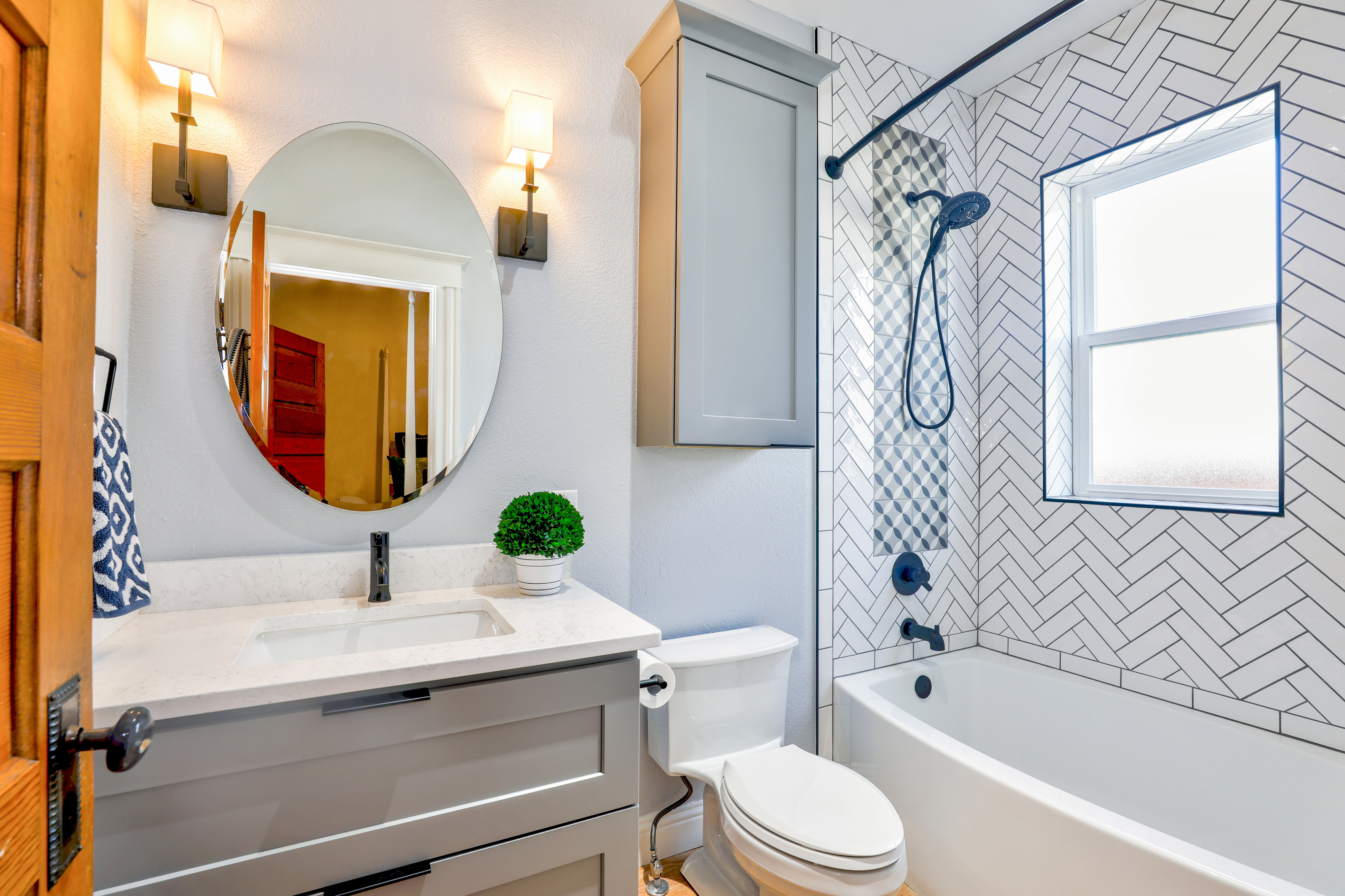 Updated interior bathroom with oval mirror and vanity with beautifully replaced shower tiles.