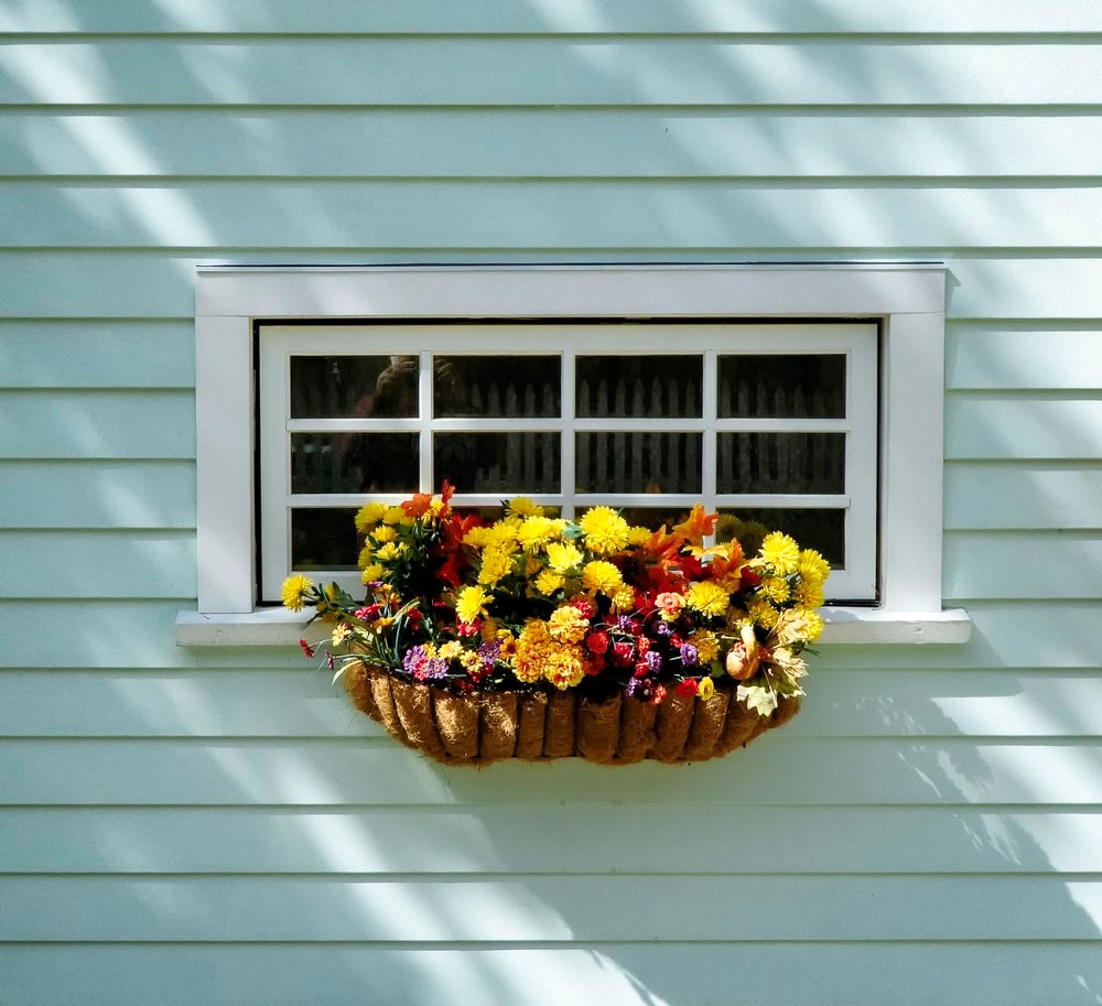 blue weatherboard home with cute flower decor hanging from the windows