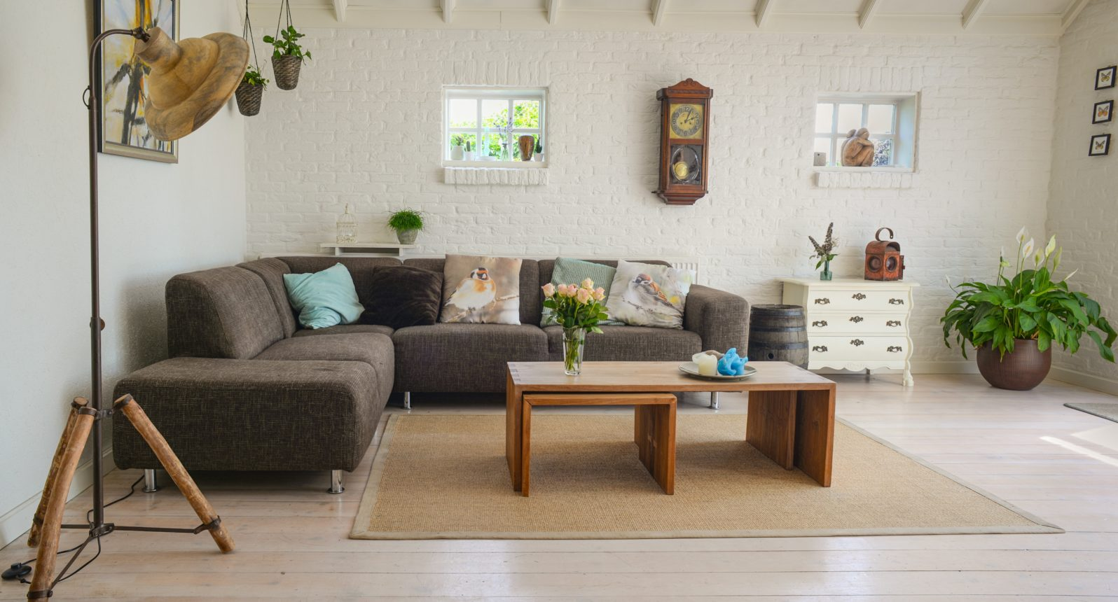 Bown wooden centre table with chase lounge and exposed beams in a cute interior designed living room
