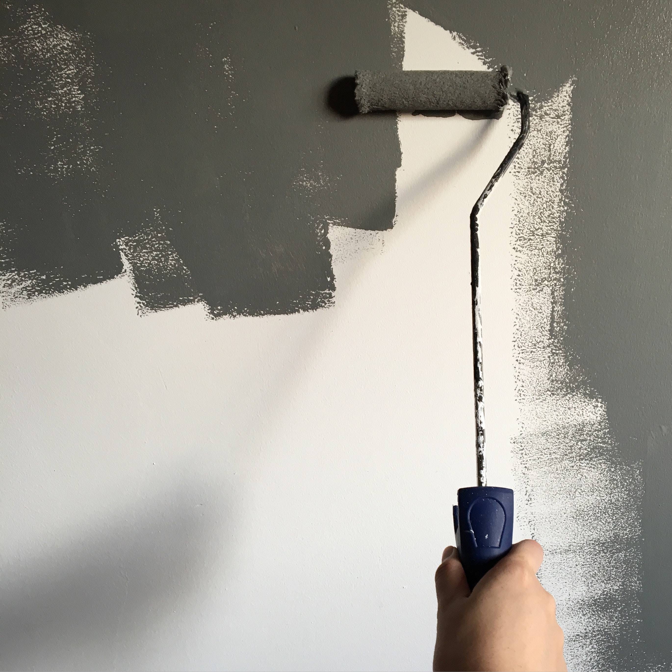 Painter holding a paint roller painting the wall grey