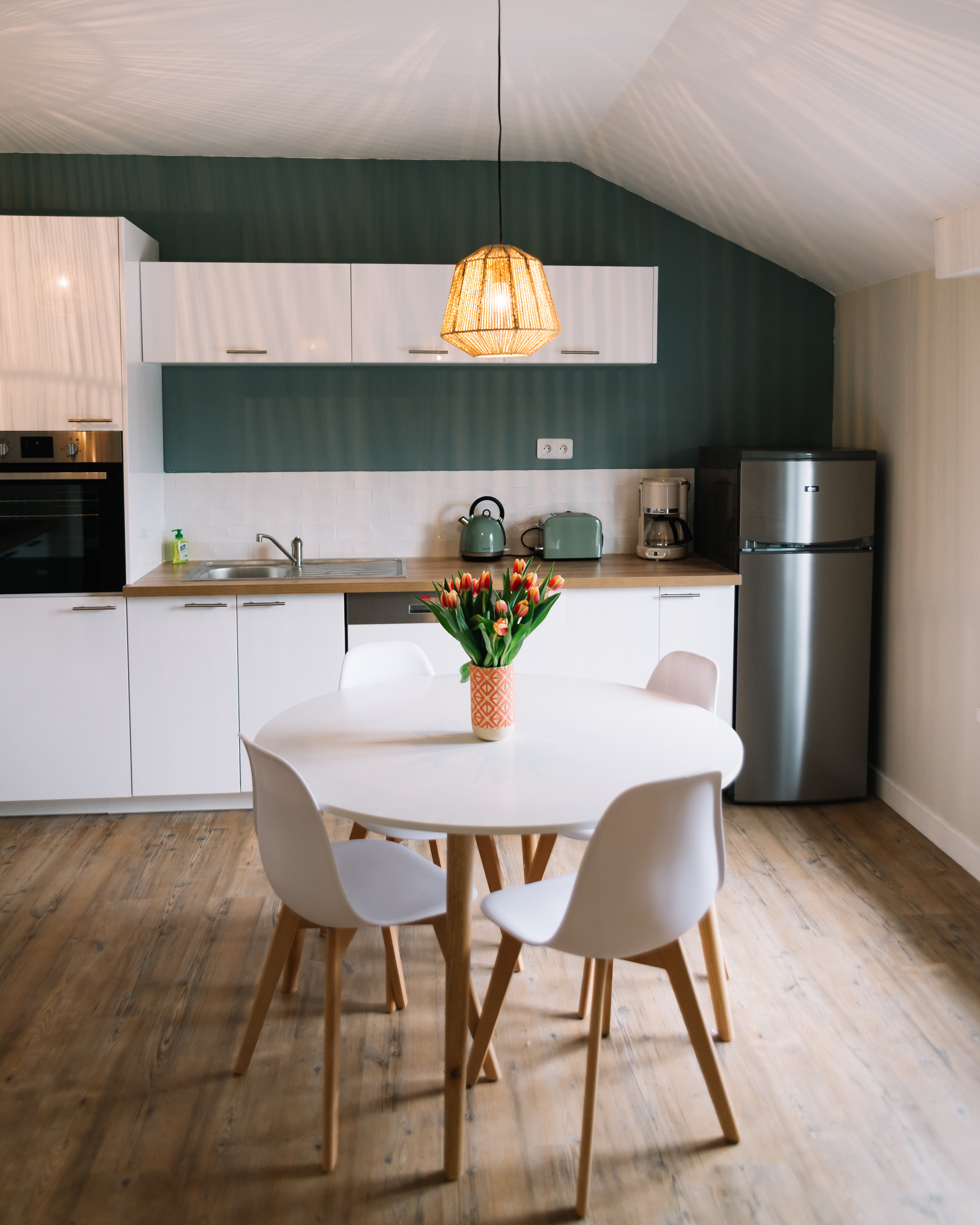 Small round dining table with four white chairs in a apartment style kitchen