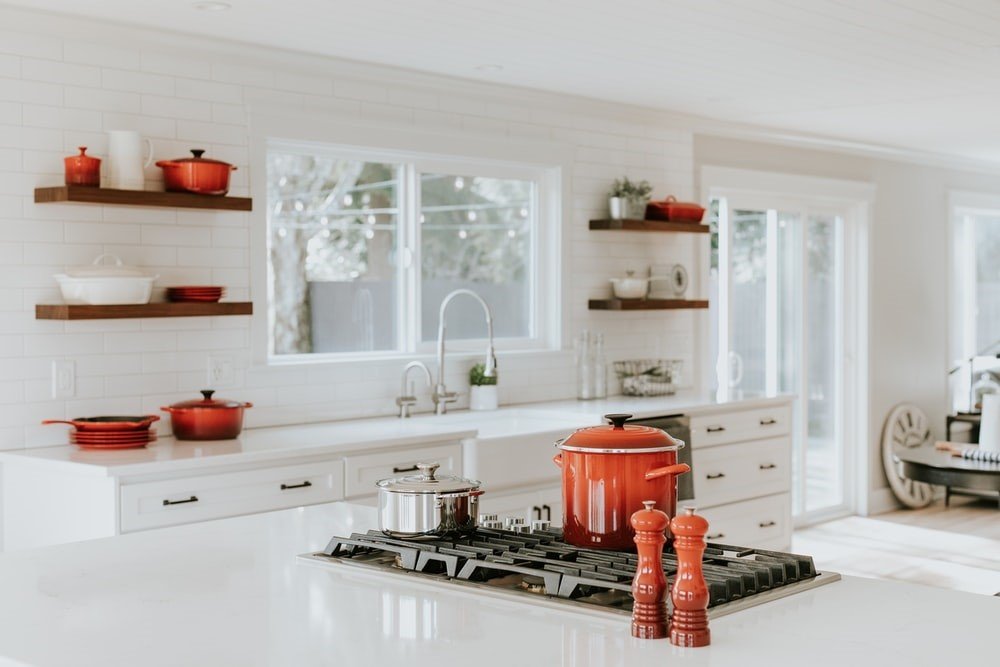 Red and White kitchen with stone bench with red crockery pots