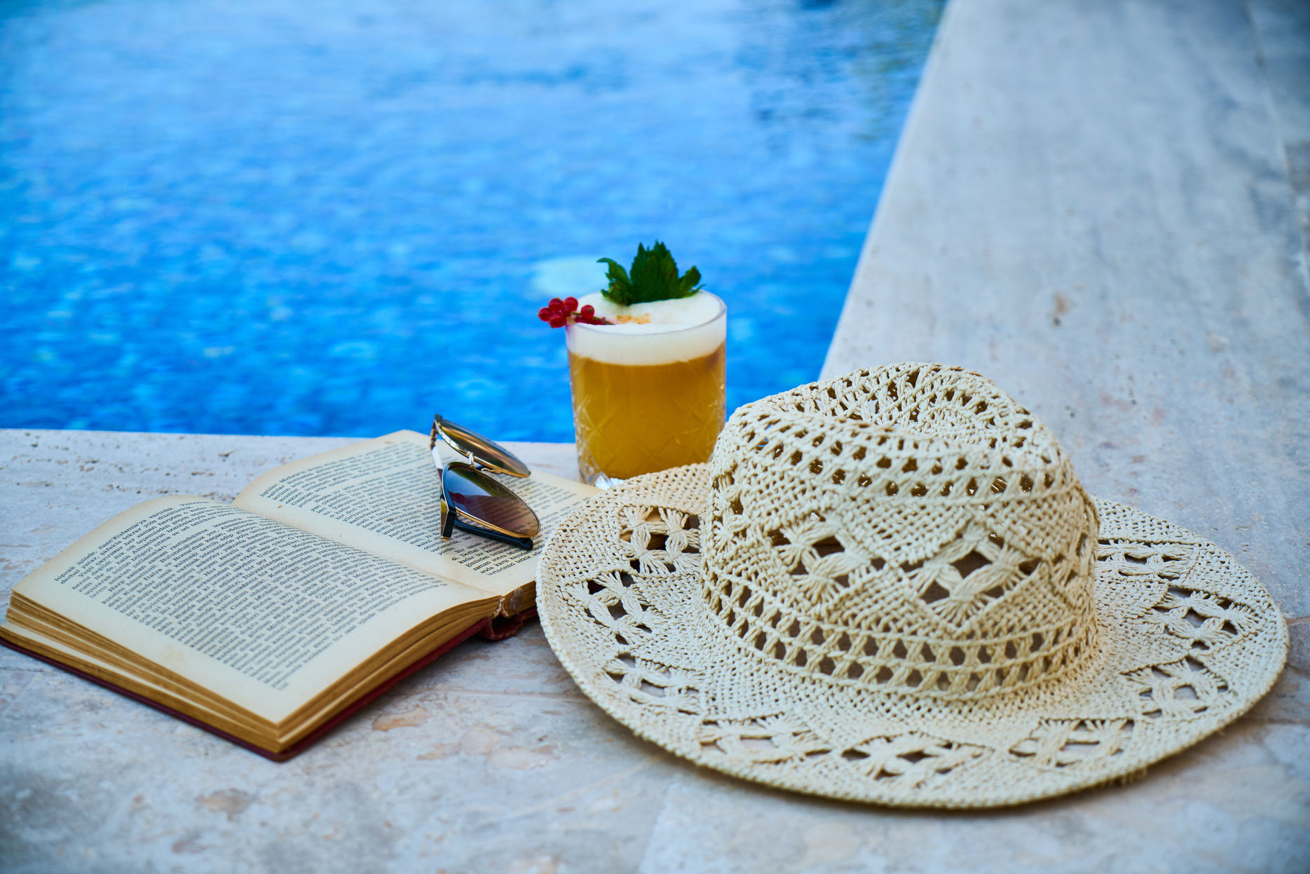 straw hat with book novel and drink beside the pool