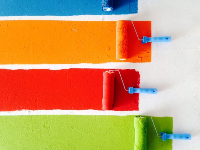 4 Paint rollers painting a wall